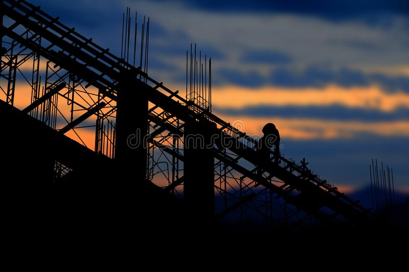 Silhouette of worker construction on industry site at concept sunrise time background with copy space add text stock image