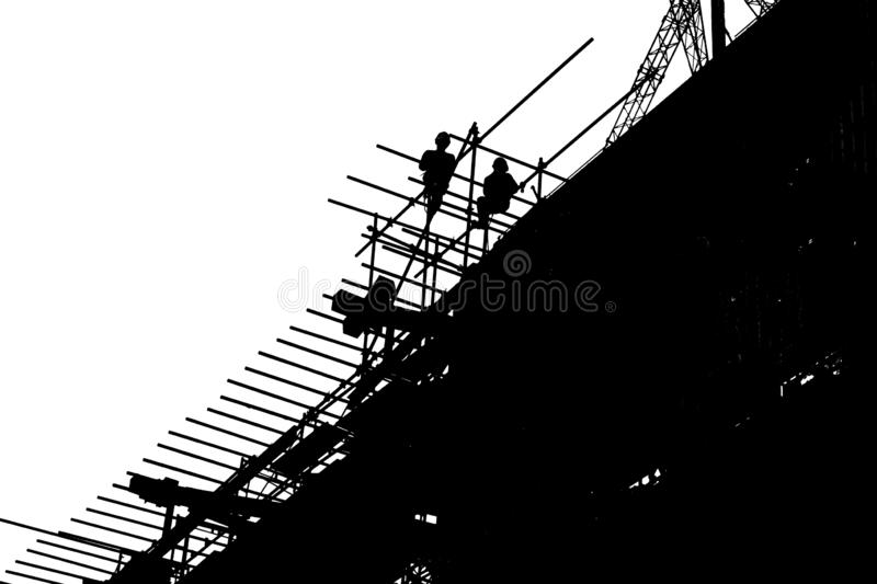 Silhouette workers constructing building at the construction site. stock images
