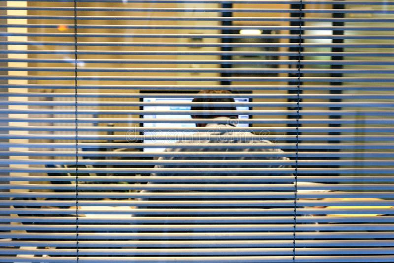 Silhouette of working late businessman man seen through windows stock images