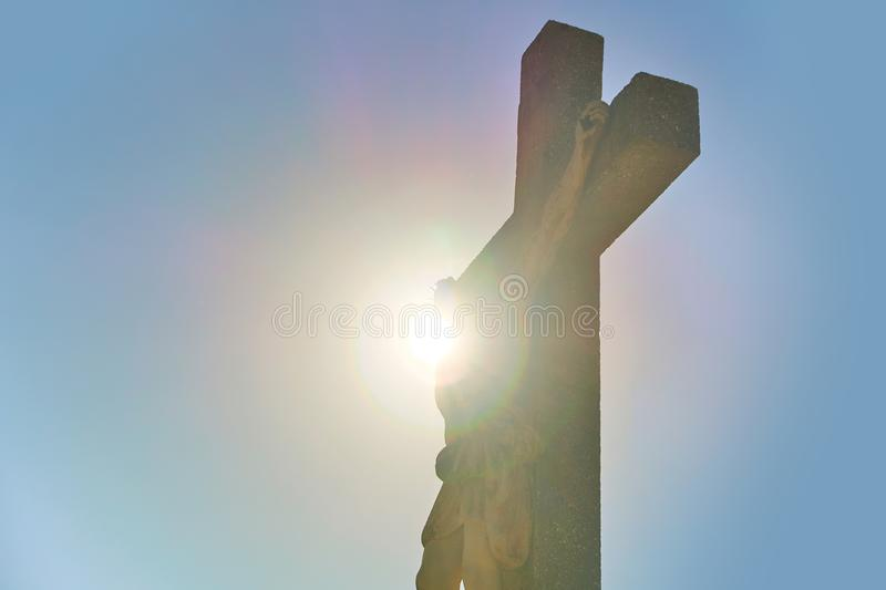 Silhouette of Jesus Christ on the worship cross with sun on background stock images