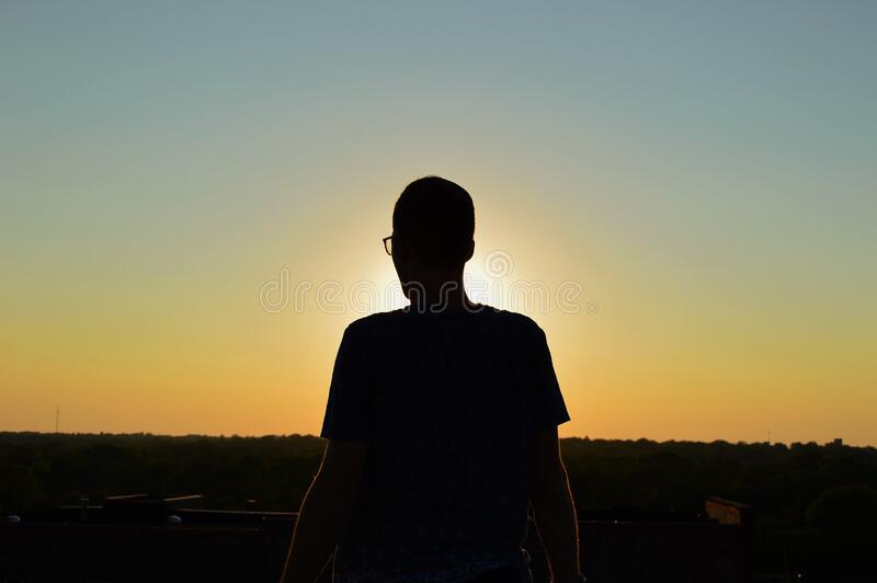 Silhouette of you man viewing sunset royalty free stock photo
