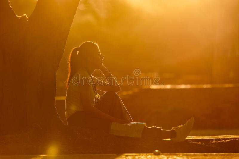 Silhouette young asian female sitting under the tree with sunset background stock images