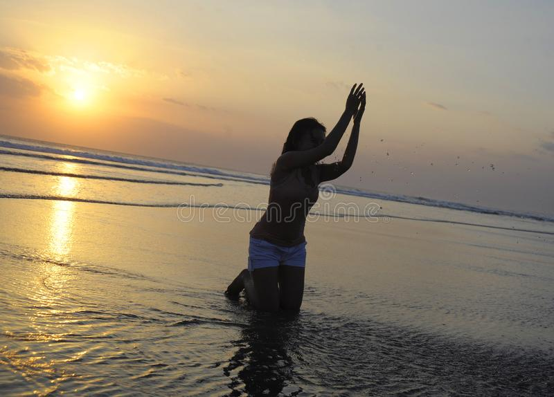 Silhouette of young Asian woman playing with sand and water on sea at sunset beach happy and excited. Under a beautiful orange sky on evening in freedom fun and royalty free stock image