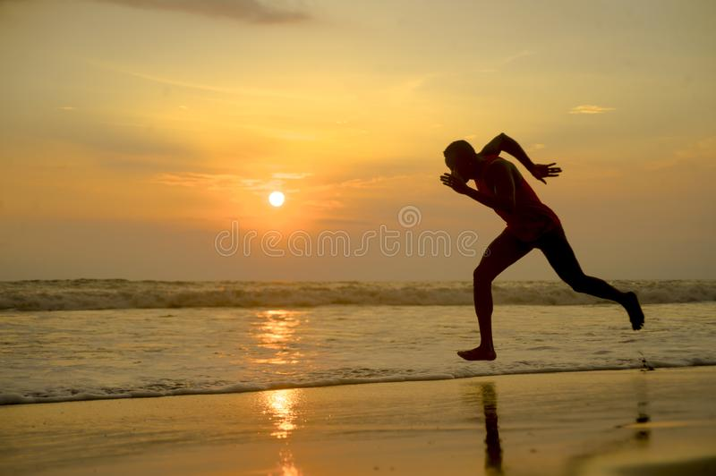 Silhouette of young attractive fit athletic and strong black African American man running at sunset beach training hard and royalty free stock photos