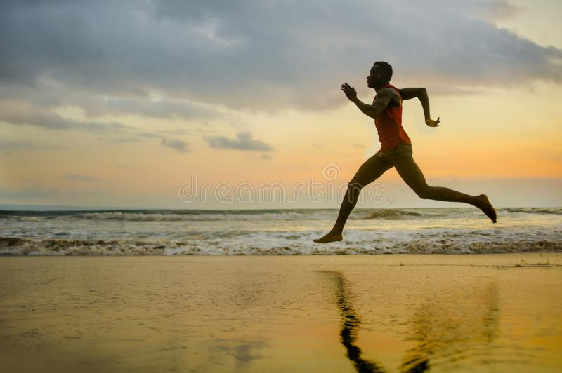 Silhouette of young attractive fit athletic and strong black African American man running at sunset beach training hard and. Sprinting on sea water in royalty free stock images