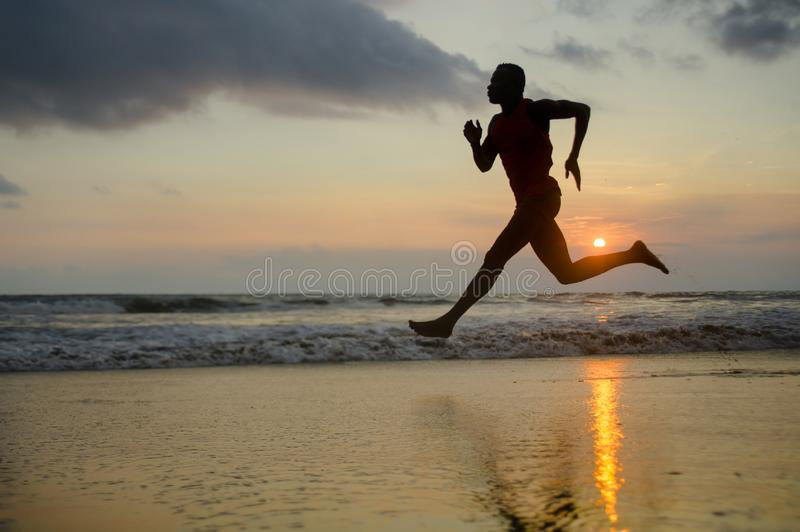 Silhouette of young attractive fit athletic and strong black African American man running at sunset beach training hard and stock photo