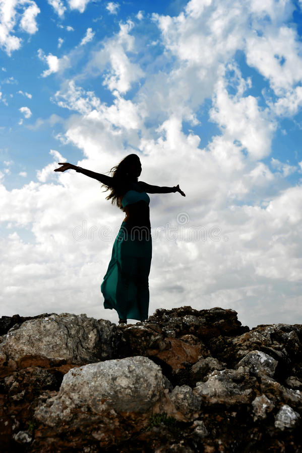 Silhouette of young attractive woman with opened arms outdoors i stock photography