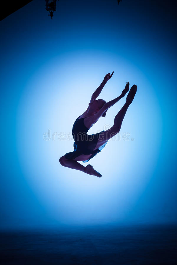 The silhouette of young ballet dancer jumping on a. The silhouette of young ballerina jumping on a blue background stock images