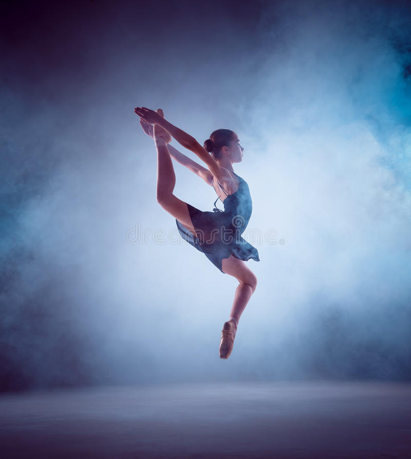 The silhouette of young ballet dancer jumping on a. The silhouette of young ballerina jumping on a blue smoke background royalty free stock photo