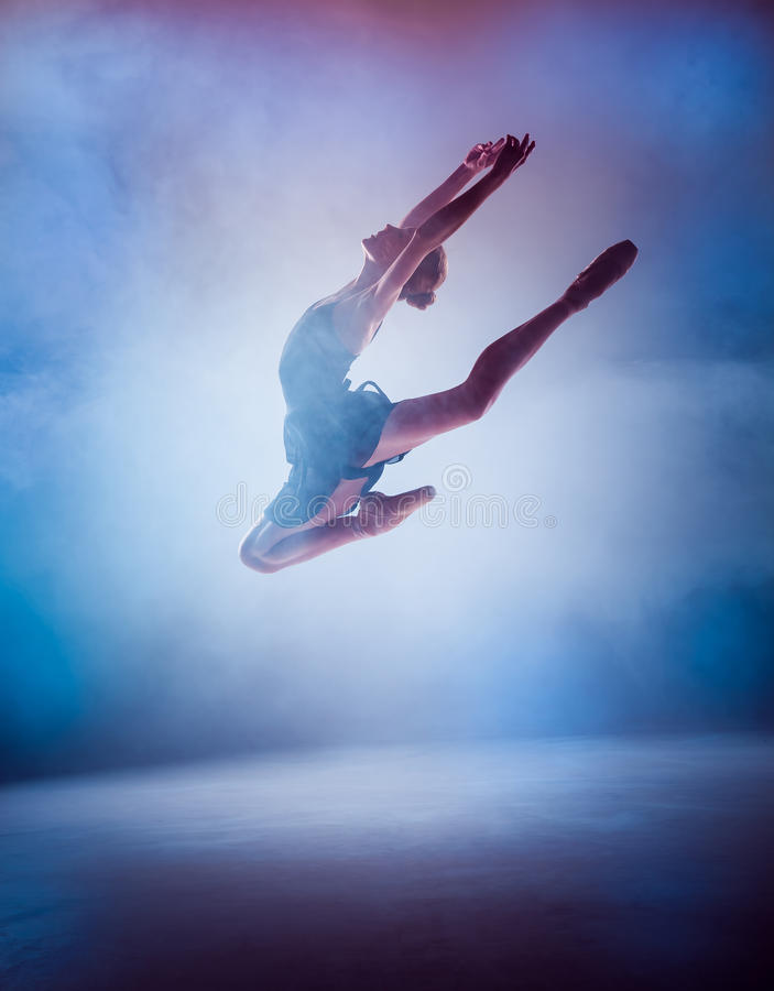 The silhouette of young ballet dancer jumping on a. The silhouette of young ballerina jumping on a blue smoke background stock photos