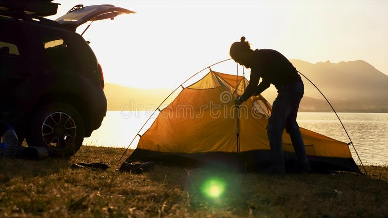 Silhouette of young bearded man sets up a tent at campsite on the lake shore. Traveler is came to the on his crossover and getting ready for the night stock images