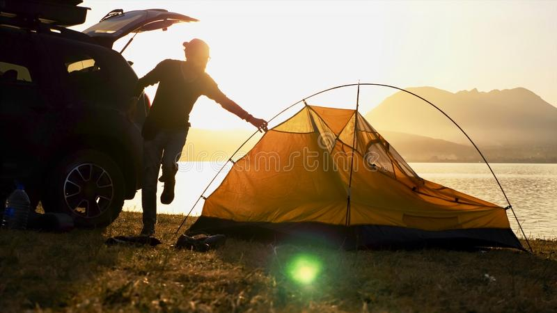 Silhouette of young bearded man sets up a tent at campsite on the lake shore. Traveler is came to the on his crossover and getting ready for the night royalty free stock photo