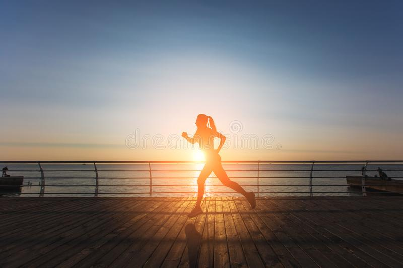 Silhouette of a young beautiful athletic girl with long blond hair in black clothes running at sunrise over the sea royalty free stock photography
