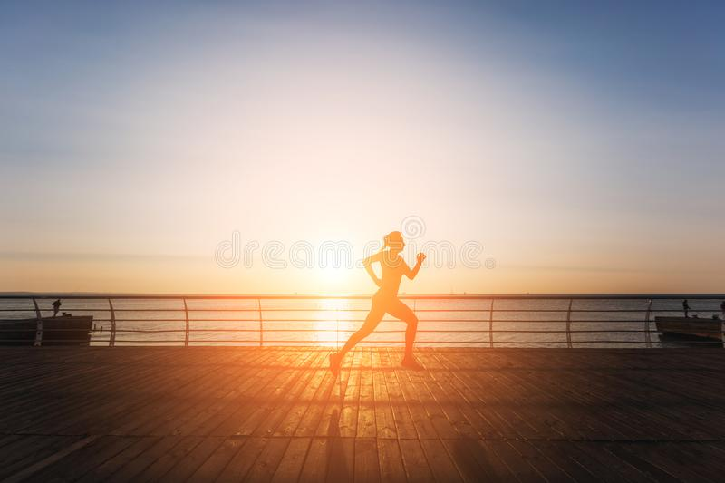 Silhouette of a young beautiful athletic girl with long blond hair in black clothes running at sunrise over the sea stock images