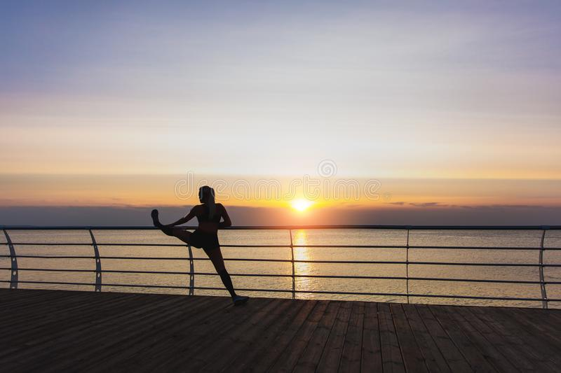 Silhouette of young beautiful athletic girl with long blond hair in headphones listening to music and doing stretching at sunrise stock image
