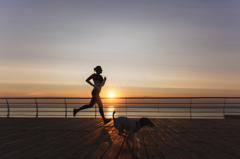 Silhouette of a young beautiful athletic girl with long blond hair in headphones that runs at dawn over the sea with her dog stock photos