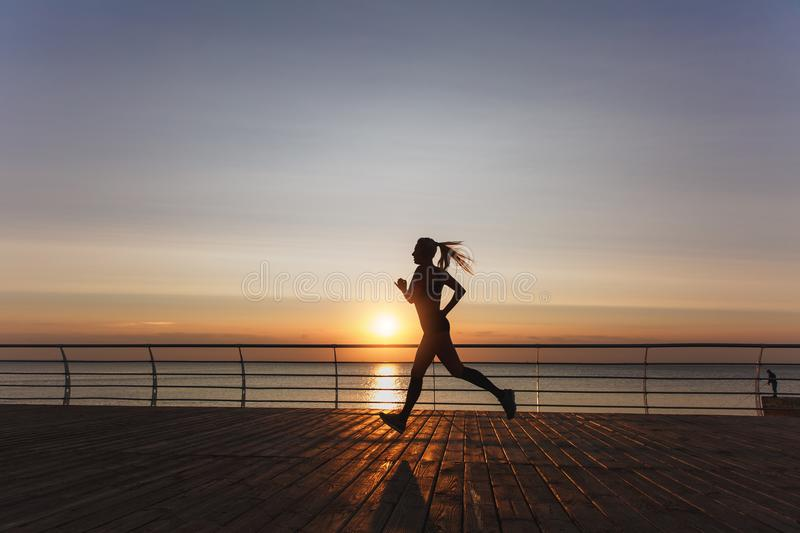Silhouette of a young beautiful athletic girl with long blond hair in headphones, who listens to music and runs at dawn over the s stock image