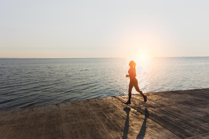 Silhouette of a young beautiful athletic girl with long blond hair in headphones, who listens to music and runs at dawn over the s royalty free stock photography
