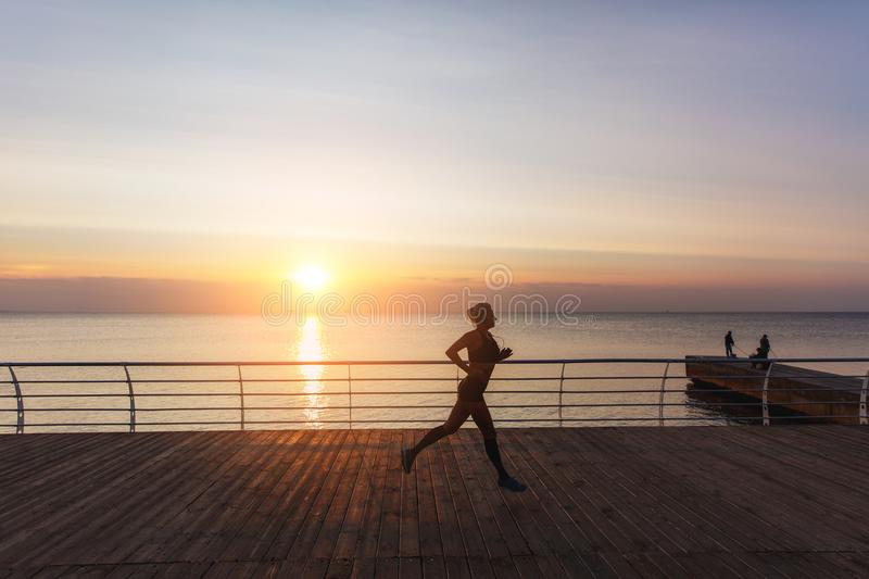 Silhouette of a young beautiful athletic girl with long blond hair in headphones, who listens to music and runs at dawn over the s stock images