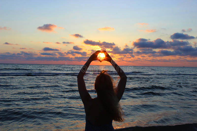 Silhouette. Young beautiful girl crossed his hands in the form of heart, through which the sun's rays make the way. stock image