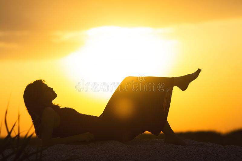 Silhouette of a young beautiful girl lying in a dress on the sand and enjoying the sunset, the figure of a woman on the beach, stock photos
