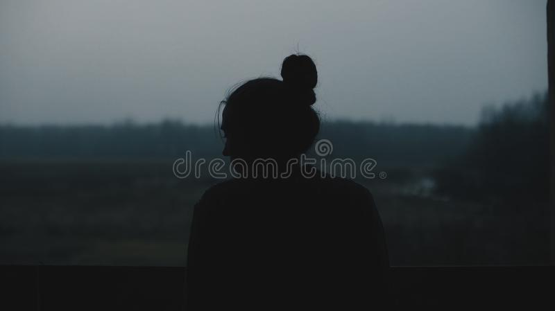 Silhouette of young beautiful girl in the village. Model on background of a forest. Woman girl in front of the window. royalty free stock image
