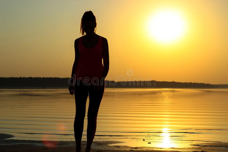 Silhouette of a young beautiful girl walking along the seashore during orange sunset royalty free stock images