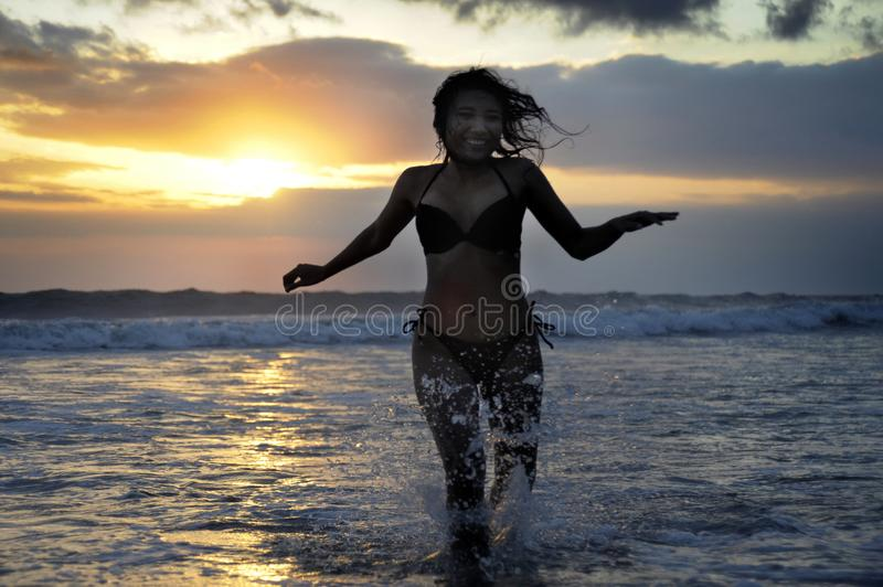Silhouette of young beautiful and asian woman running free and happy having fun at sunset beach in Bali stock image