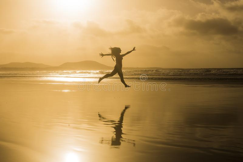 Silhouette of a young beautiful woman jumping at the beach by the shore. Sunset. Yellow sky. Lanzarote, Canary islands stock photos