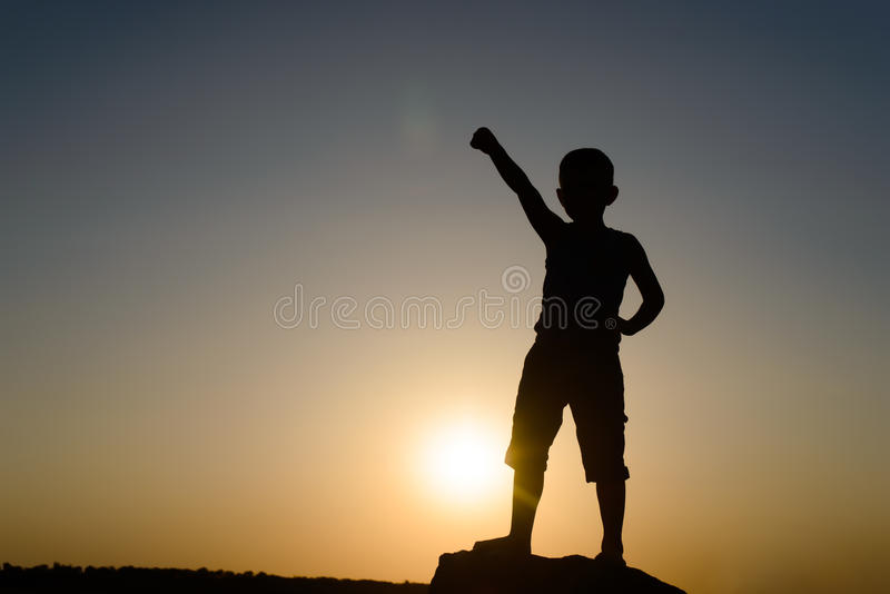 Silhouette of Young Boy with Fist Raised in Air. Silhouette of Young Confident Boy with Arm Raised in Air in Fist, Backlit By Late Day Sun with Copy Space stock photo
