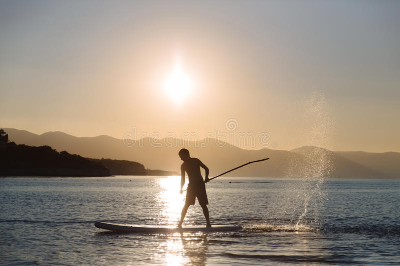 Silhouette of young boy paddle boarding at sunset. concept lifestyle sport royalty free stock image