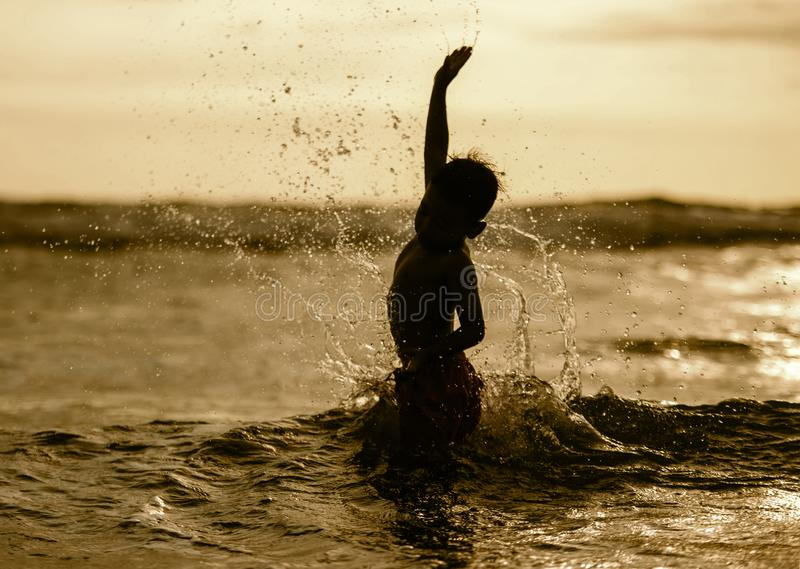 Silhouette of young boy playing crazy happy and free at the beach splashing with water playing with sea waves jumping and having royalty free stock photography