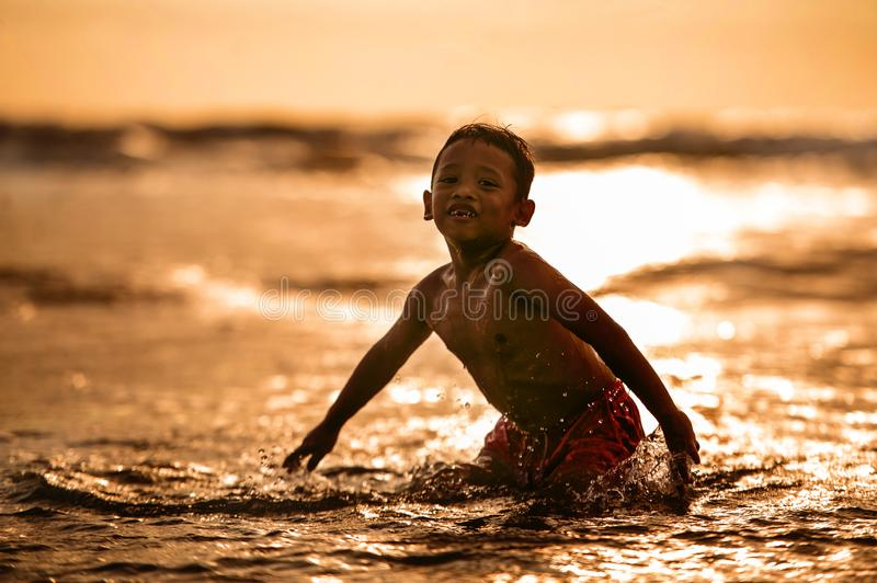 Silhouette of young boy playing crazy happy and free at the beach splashing with water playing with sea waves jumping and having royalty free stock image