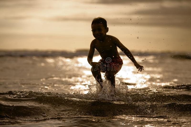 Silhouette of young boy playing crazy happy and free at the beach splashing with water playing with sea waves jumping and having royalty free stock photos