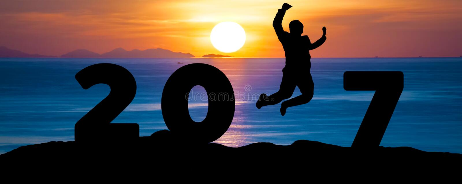 Silhouette young business man jumping on sea and 2017 years while celebrating new year stock photos