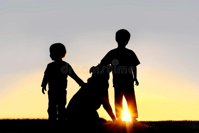Silhouette of Young Children with Dog. A silhouette of two children; a little boy and his toddler brother standing outside at sunset, petting their German stock photos