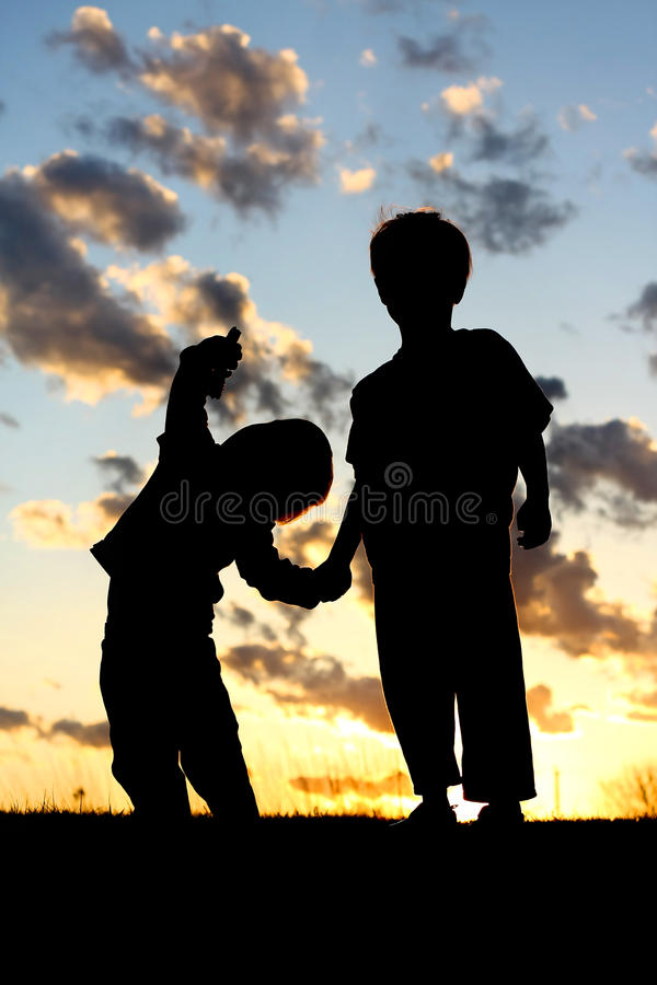 Silhouette of Young Children Holding Hands at Sunset. A silhouette of two young children; a little boy and his baby brother, lovingly holding hands in front of a stock images
