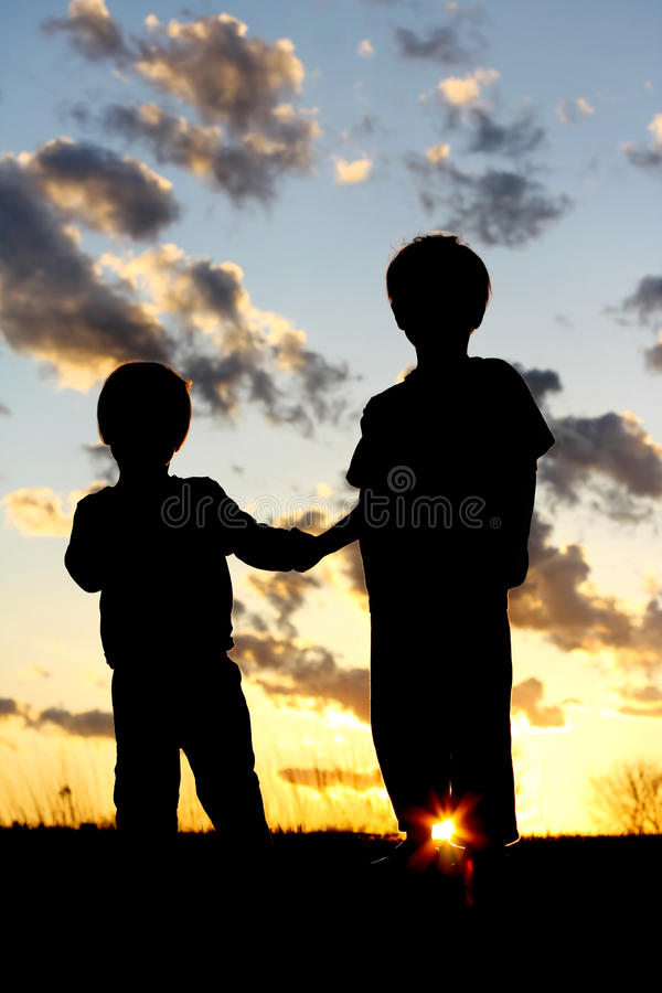 Silhouette Young Children Holding Hands at Sunset. A silhouette of two young children; a little boy and his baby brother, lovingly holding hands in front of a stock image