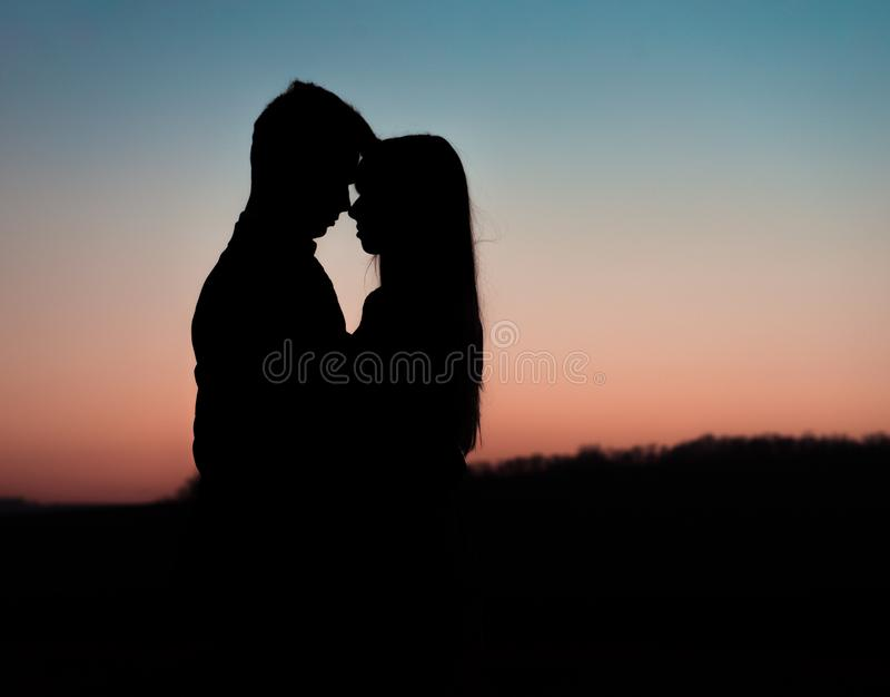 Silhouette of young couple on background of sunset. Silhouette of young couple on background of sunset royalty free stock image