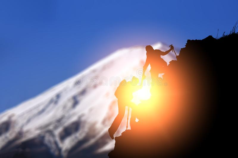 Silhouette Young couple  hikers climbing up on the peak of mountain. Climbing ,Helps and Team work concept stock image