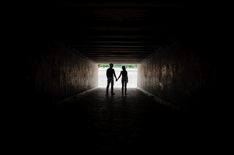 Silhouette of young couple holding hands stock image