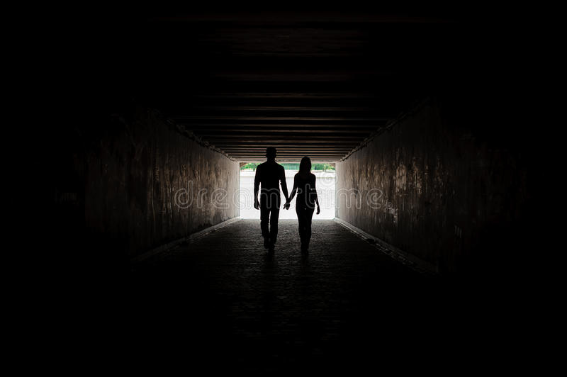 Silhouette of young couple holding hands stock photography