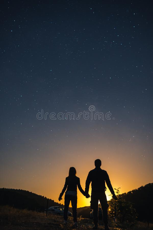 Silhouette of young couple holding hands under stars. The concept on the theme of love. romantic evening together, sunset,. Vertical royalty free stock images