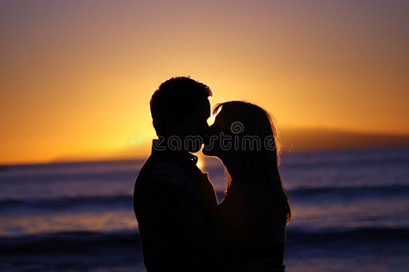 Silhouette of a young couple kissing at the beach royalty free stock image