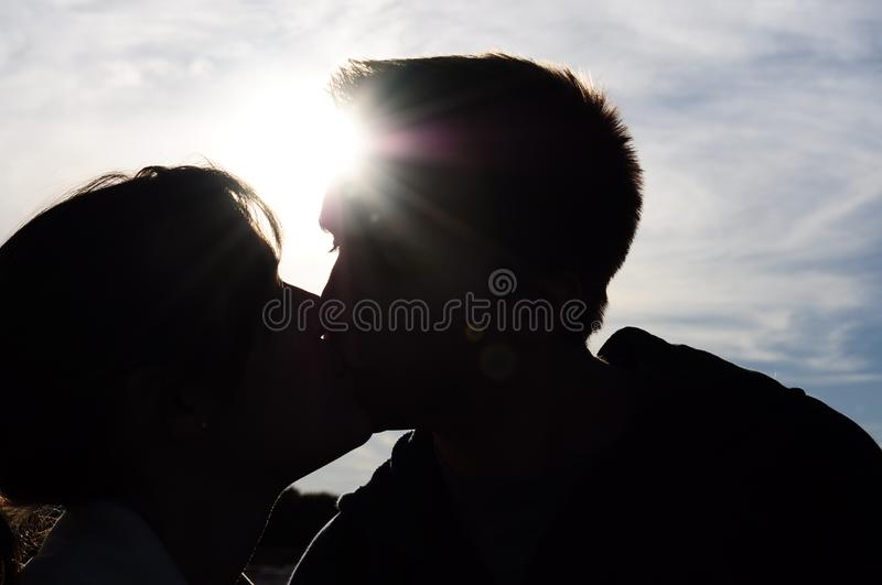 Silhouette of Young Couple Kissing. A young couple kisses, silhouetted by the sun and sky. Lens flare and slight detail in people royalty free stock photography