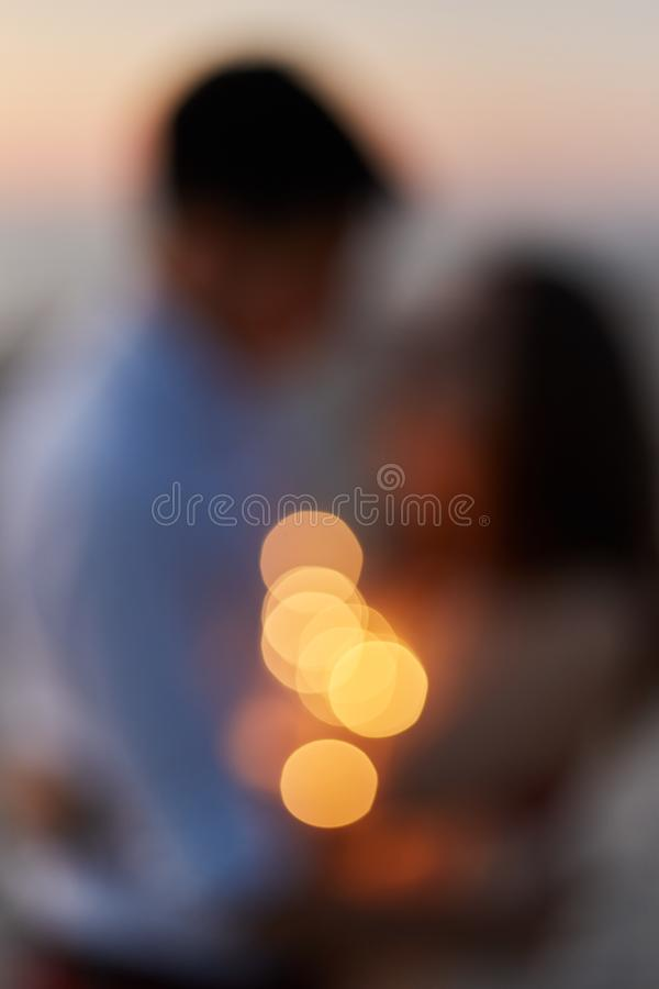 Silhouette of a young couple kissing on the seashore at sunset. Blurred background. royalty free illustration