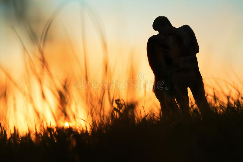 Silhouette of a young couple kissing at sunset royalty free stock images