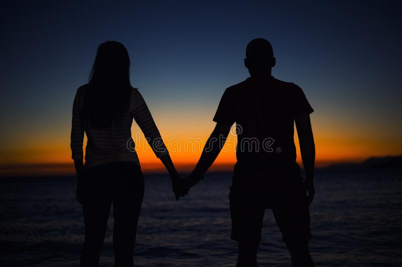 Silhouette of young couple in love at the beach stock images