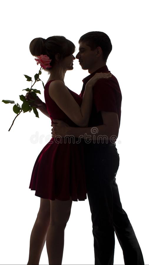 Silhouette of a young couple in love dance on white isolated background, man hugging woman holding rose flower, concept romance royalty free stock photography