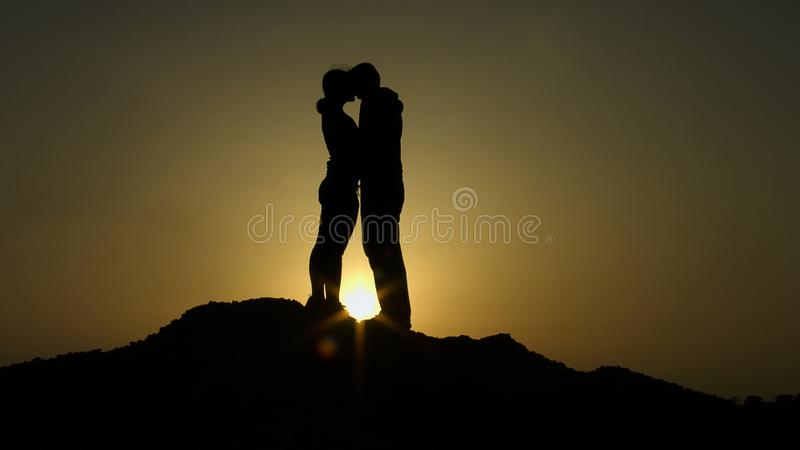 Silhouette of young couple in love hugging, kissing in sunset rays on mountain royalty free stock photos